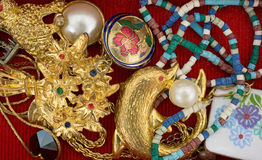 Goupilles et bijoux sur la vue supérieure de fond rouge photographie stock libre de droits