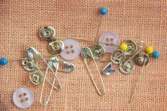 Goupilles et boutons pour coudre sur un fond de toile Photographie stock libre de droits