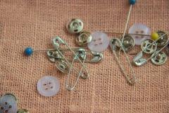 Goupilles et boutons pour coudre sur un fond de toile Photo stock