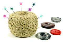 Goupilles pour coudre avec la bobine des fils et des boutons de couleur sur un fond blanc Image stock