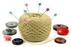 Goupilles pour coudre avec la bobine des fils et des boutons de couleur sur un fond blanc Images stock