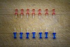 Goupilles rouges et bleues sur une table en bois Image stock