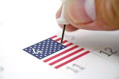 Goupilles sur un calendrier le 4 juillet avec le drapeau des Etats-Unis Photographie stock libre de droits