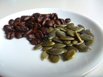 Gourd seed with coffee beans on a white plate Royalty Free Stock Images