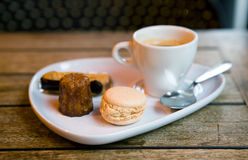 Gourmand coffee in a Parisian cafe. Served with traditional French sweets - macaroon cookie, eclair pastry and canele Stock Photo