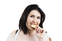 Gourmand young woman portrait. Eating a cookie, dark hair, close up, isolated on white, studio shoot Royalty Free Stock Image