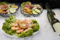 Gourmet. Shrimps salad and bottles closeup Stock Image