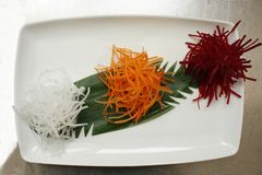 Red beet and carrot grated and rise noodles on a green leaf on a white plate. Diagonal gourmet setting. Natural raw food colors. royalty free stock image