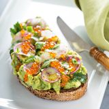 Gourmet avocado toast with caviar and radishes Stock Photography