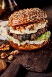 Gourmet beef burger with walnuts and cheese. Gourmet beef burger with walnuts and melted cheese on a rustic wooden board with shelled nuts in the foreground and Royalty Free Stock Photography