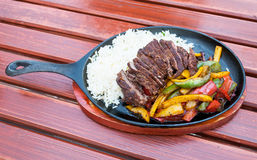 Gourmet beef dish. Gourmet dinner meal served in a frying pan with steamed vegetables Stock Photography