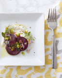 Gourmet Beet Salad Table Setting. A table setting depicting an artfully plated beet salad dressed in oil, flowers, herbs and alongside a smear of yogurt or Stock Images