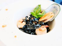 Gourmet breakfast meal black pasta seafood. Concept. luxury food. delicacy recipe royalty free stock images