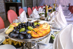 Gourmet buffet table set with fruit and sweets. Grapes, apples, Stock Photography