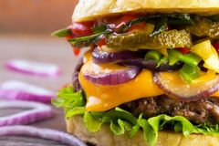 Gourmet burger closeup. Juicy burger closeup with roasted vegetables and grilled beef putty Stock Photos