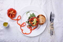 Gourmet burger with pepper, arugula and avocado on white plate over cotton tablecloth. Top view. Royalty Free Stock Photo