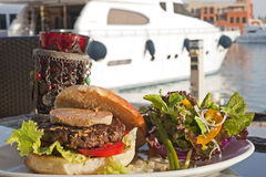 Gourmet burger with salad in a private marina Stock Image