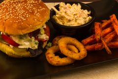 Gourmet burger in sesame seeded brioche bun. Gourmet beef burger, with salad, blue cheese sauce, sweet potato fries, onion rings and coleslaw stock images