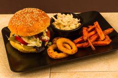 Gourmet burger in sesame seeded brioche bun. Gourmet beef burger, with salad, blue cheese sauce, sweet potato fries, onion rings and coleslaw stock image
