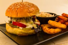 Gourmet burger in sesame seeded brioche bun. Gourmet beef burger, with salad, blue cheese sauce, sweet potato fries, onion rings and coleslaw royalty free stock images
