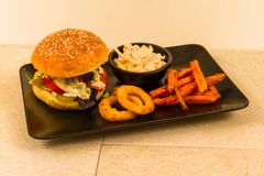 Gourmet burger in sesame seeded brioche bun. Gourmet beef burger, with salad, blue cheese sauce, sweet potato fries, onion rings and coleslaw royalty free stock image