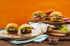 Gourmet burgers. Five gourmet burgers on bright orange background Royalty Free Stock Images