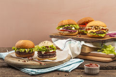 Gourmet burgers. Five different gourmet burgers on wooden background Royalty Free Stock Photos