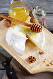 Gourmet cheese Brie with honey on a cutting board Stock Image