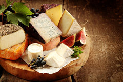 Gourmet cheese platter with fresh figs. And grapes amongst an assortment of speciality soft and semi-hard cheeses on a rustic wooden table, close up high angle Stock Photos