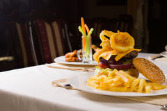 Gourmet Cheeseburger and French Fries on Table Stock Image