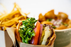 Gourmet Cheeseburger with Fries and Chili in Background Stock Image