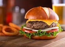 Gourmet Cheeseburger Pretzel Bun. A delicious gourmet cheeseburger on a pretzel bun with lettuce, onion, and tomato Stock Photos