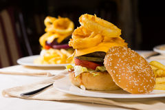 Gourmet Cheeseburgers Piled High with Toppings Stock Photo