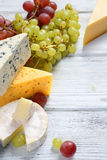 Gourmet cheeses with grapes Royalty Free Stock Photos