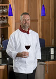 Gourmet Chef. Chef standing in kitchen holding a glass of red wine stock images