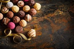 Gourmet chocolate Valentines still life. With a large selection of luxury handmade chocolates with a single heart shaped bonbon on a twirled ribbon symbolising royalty free stock photos