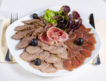 Gourmet cold meat platter on a buffet. With assorted smoked and processed meats garnished with fresh lettuce and olives, high angle view Royalty Free Stock Photos