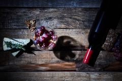 Gourmet composition of wineglass with grapes and walnuts on wood table with cheese and bottle of red wine.  royalty free stock photos