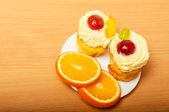 Gourmet cream cake cookie and orange on plate Royalty Free Stock Photos