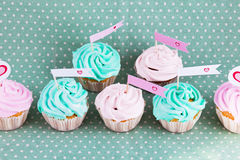 Gourmet cream cupcakes with hearts. Cupcakes with hearts on green background for valentine day Royalty Free Stock Photo