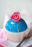 Gourmet cupcake. Cupcake decorated with gold embossing and a sugar rose stock photos