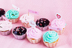 Gourmet cupcakes with hearts. Choloate cupcakes with hearts on pink background Stock Photography