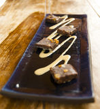 Gourmet desert. Stylish gourmet dessert of chocolate cake on wood table in restaurant Stock Photos