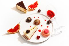 Gourmet desserts and grapefruit slices on a white plate. Top view stock photos