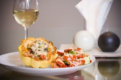 Gourmet dinner. Dinner plate with stuffed squash and vegetable salad and a glass of white wine Royalty Free Stock Photo