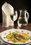 Gourmet dinner with a glass of white wine. Jug of white wine on a red background stock photography