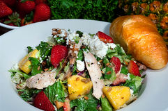 Gourmet Dinner Salad with Fresh Baked Croissant. A gourmet salad in a white bowl with fresh baked croissant and fruits and vegetables in the background Stock Photography
