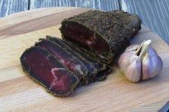 gourmet Doftande torkat kött som strilas med kryddor och snittet in i tunna skivor, och ett huvud av vitlök på ett träbräde mörkt arkivfoton