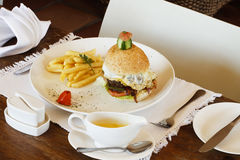 Gourmet egg hamburger and chips Royalty Free Stock Images
