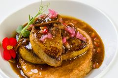 Foie gras with fig sauce. Gourmet foie gras with fig sauce in white plate stock photos